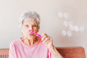 An elderly woman in a nursing home blowing bubbles.