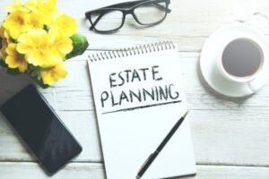 An estate planning written on a notepad with glasses.